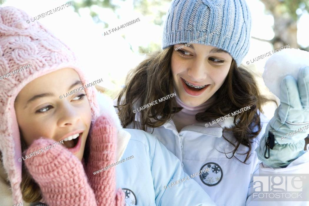 Stock Photo: Two teenage girls smiling, one holding up snowball, both dressed in winter clothing.