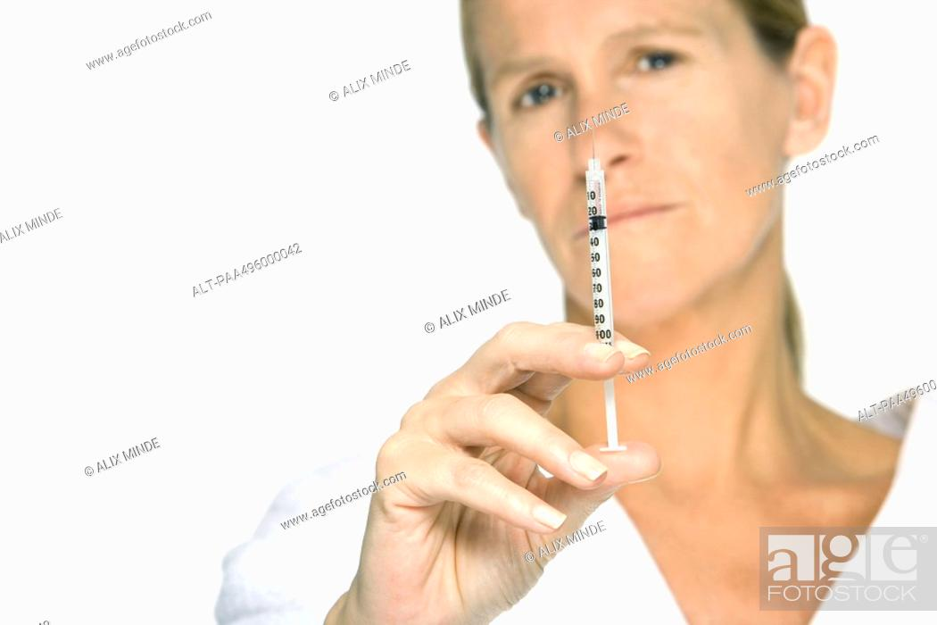 Stock Photo: Woman holding up syringe, looking at camera.