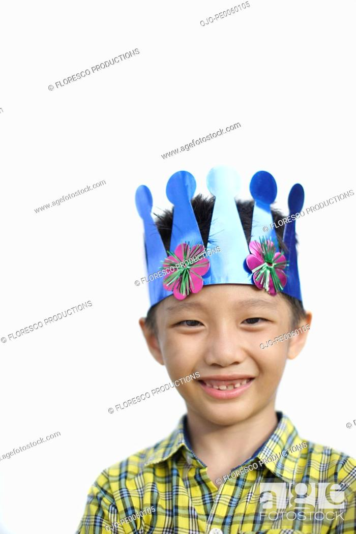 Stock Photo: Young boy indoors wearing party hat smiling.