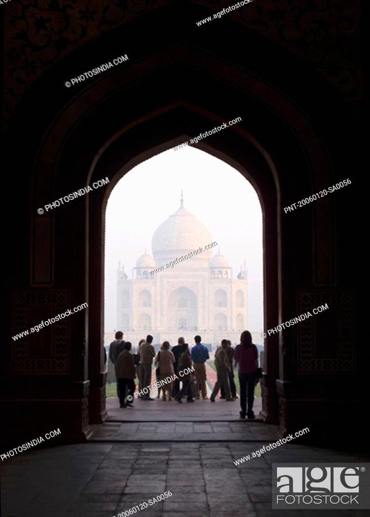 Stock Photo: Tourist standing in front of a mausoleum, Taj Mahal, Agra, Uttar Pradesh, India.