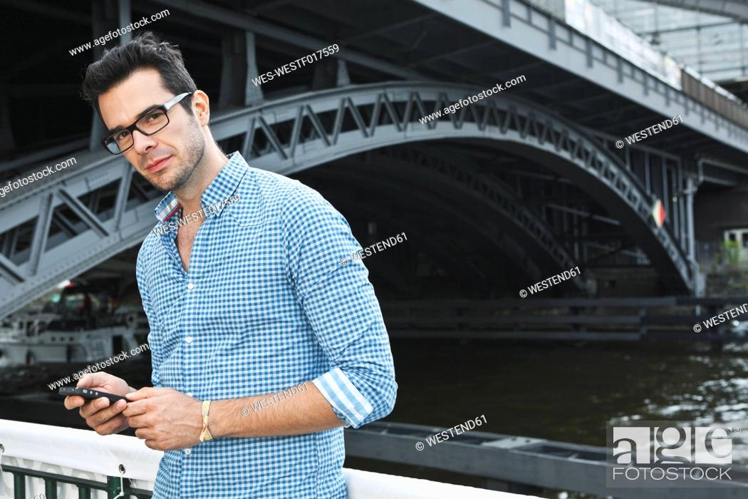 Stock Photo: Germany, Berlin, Man using cell phone in front of bridge.