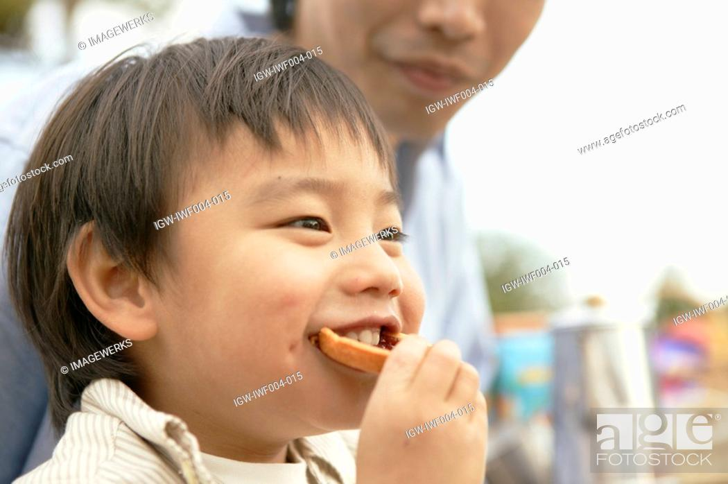 Stock Photo: A small boy takes a bite of a foodstuff.