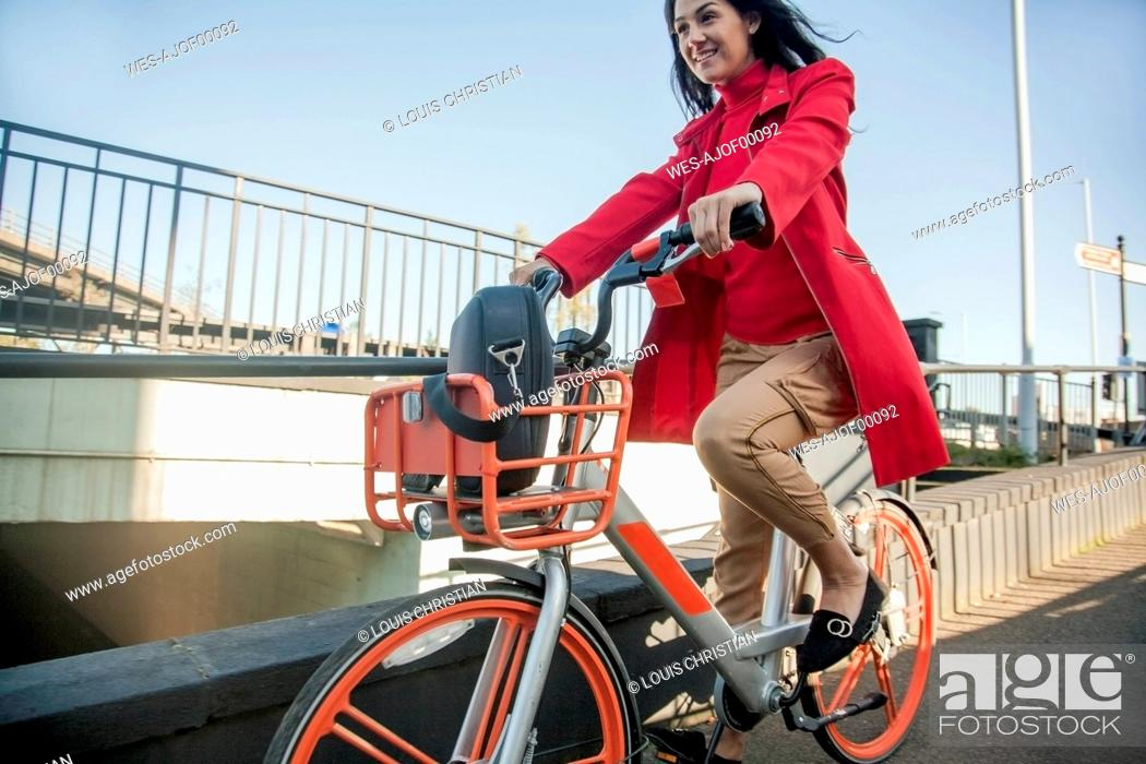 Stock Photo: Young woman riding through the city on a rental bike.