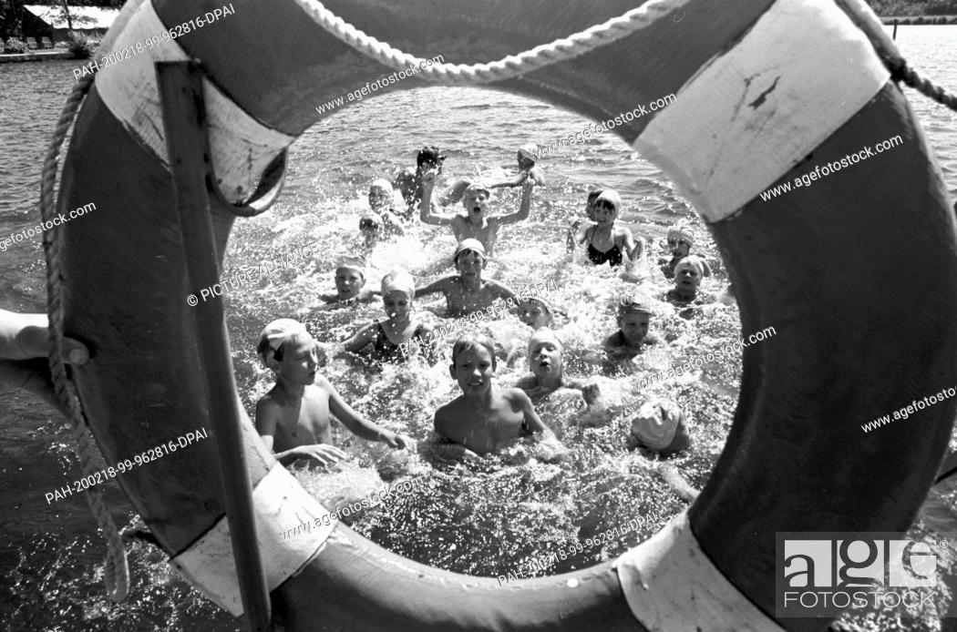 Stock Photo: 07 July 1989, Saxony, Torgau: In the summer of 1989, children can be seen in the water of a forest pool near Torgau through a life belt.
