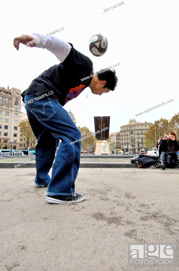 Stock Photo: Boy playing with a ball, Plaça de Catalunya, Barcelona, Catalonia, Spain.