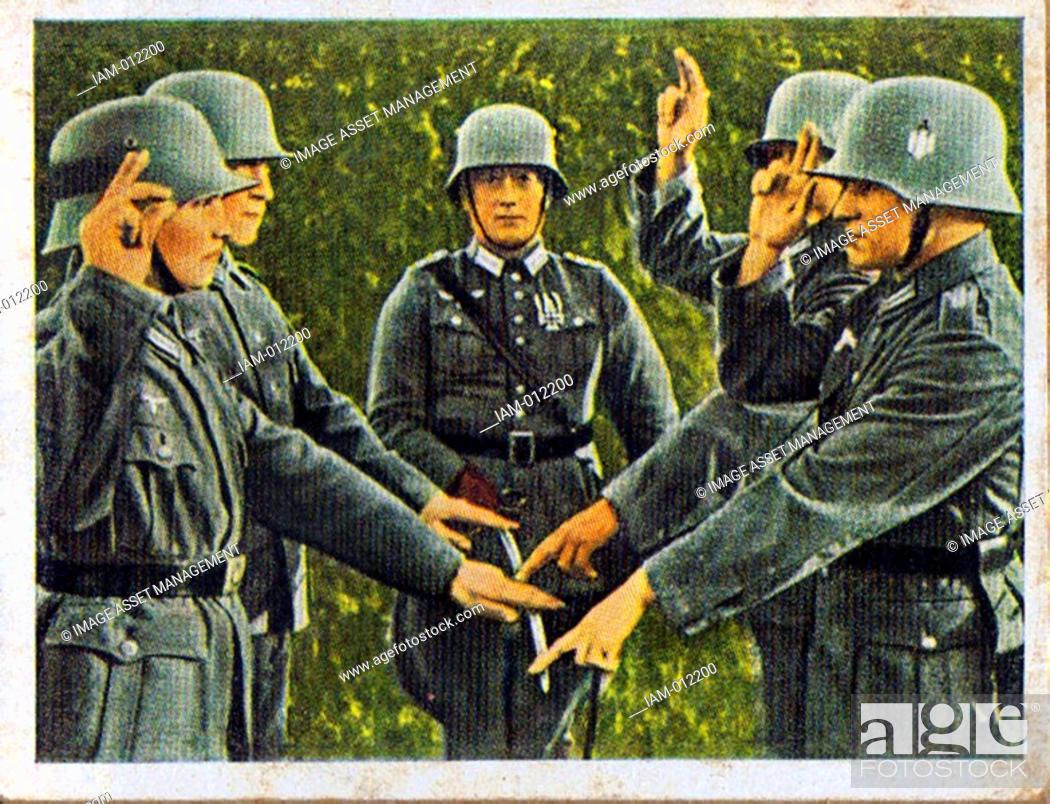 Stock Photo: German re-armament and militarisation: German army recruits taking their oath of loyalty on the flag. From series of 270 cigarette cards 'Die Deutsche.