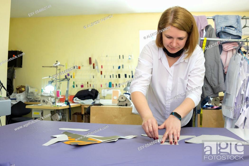 Stock Photo: Girl fashion designer puts chalk details on patterns.