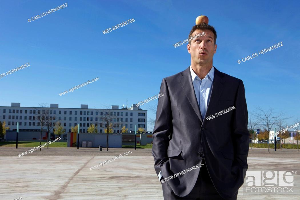 Stock Photo: Germany, Bavaria, Munich, Businessman with apple on his head.