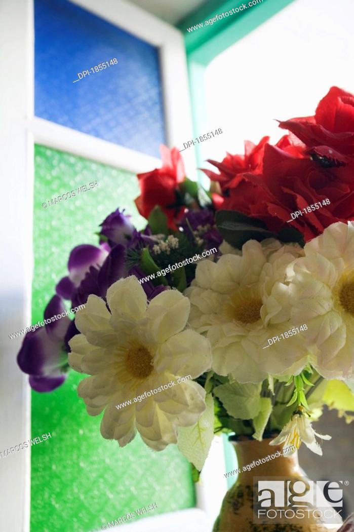 Stock Photo: Plastic flowers on window sill.