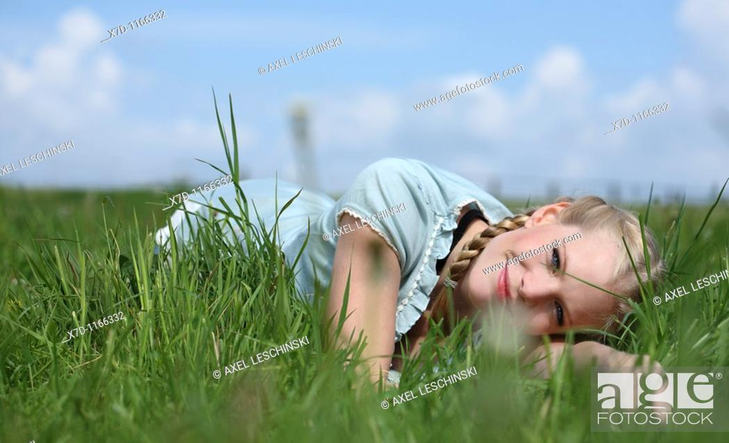 Stock Photo: Young blond woman lying on meadow.