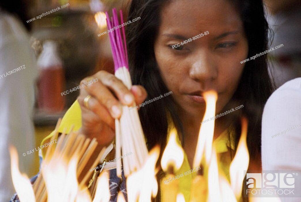Stock Photo: Thailand, Bangkok, Yarowat Chinatown, Wat Mangkon Kamalawat, Vegetarian Festival, Woman lighting candles as an offering.