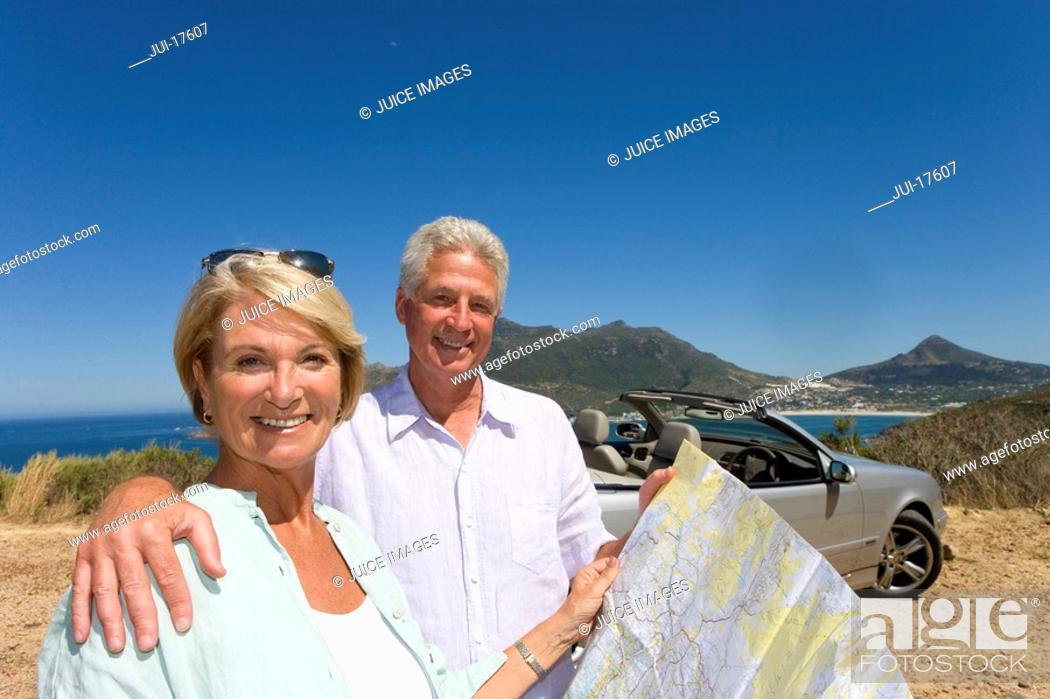 Stock Photo: Couple looking at map on coastal highway.
