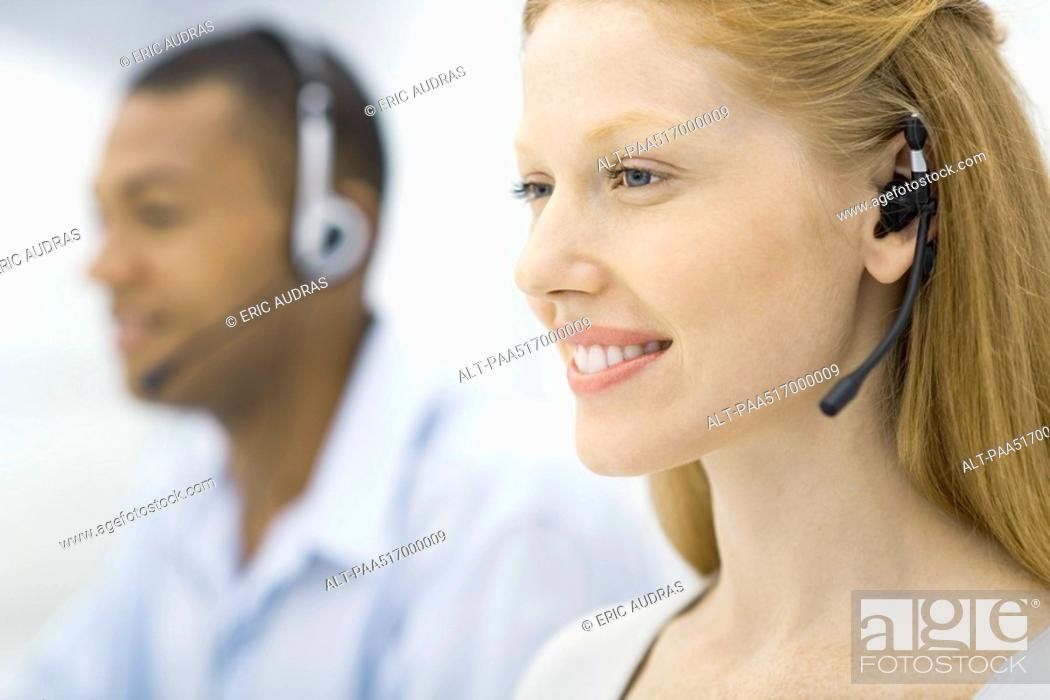 Stock Photo: Woman wearing headset, male colleague in background, both working, smiling.