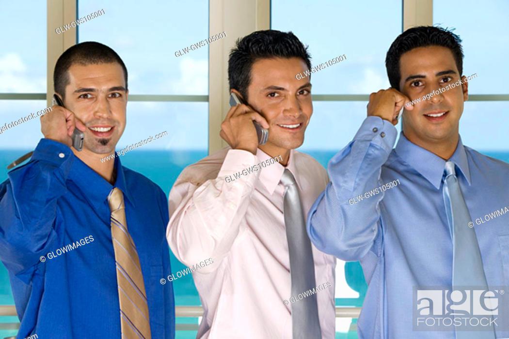 Stock Photo: Portrait of three businessmen using mobile phones.