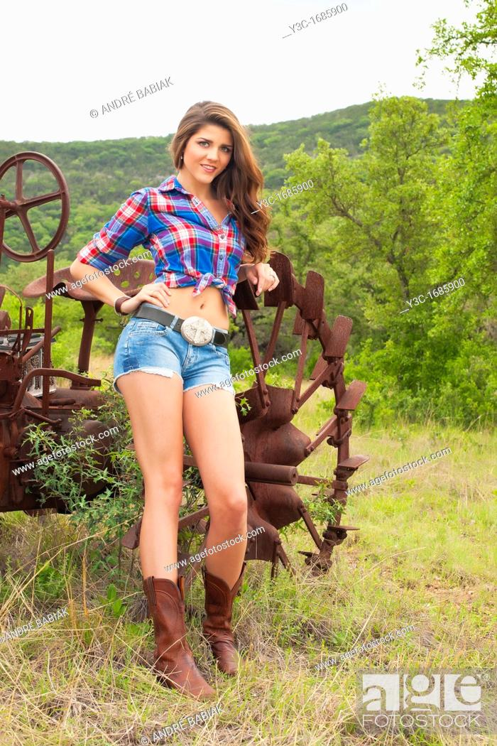 Stock Photo: American country girl posing in front of old rusty tractor.