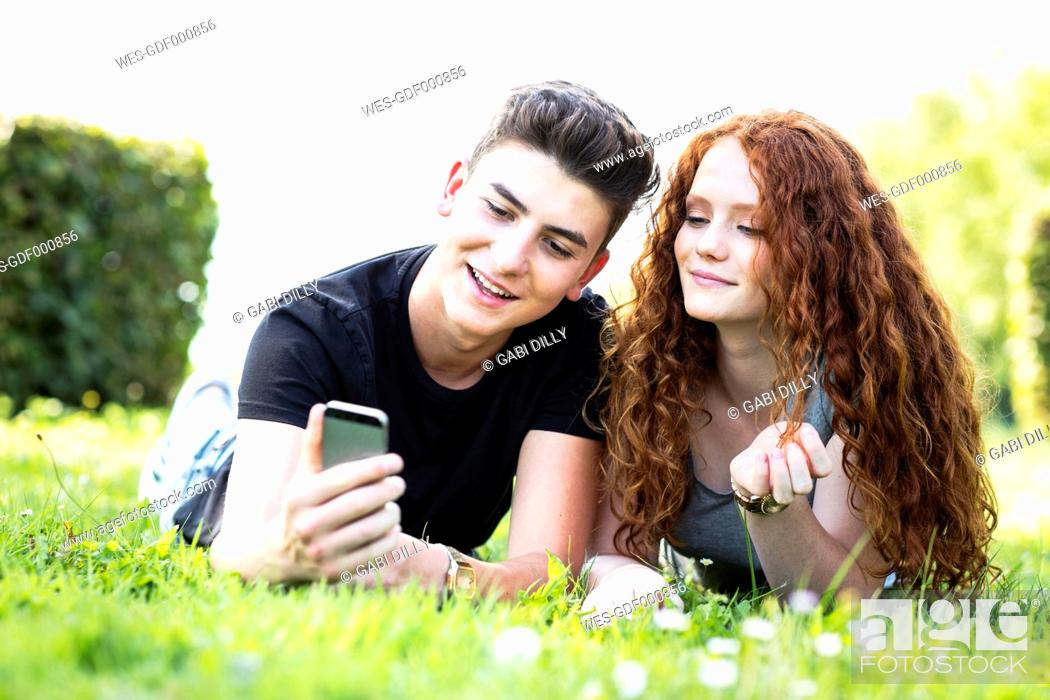 Stock Photo: Teenage couple lying on a meadow looking at smartphone.
