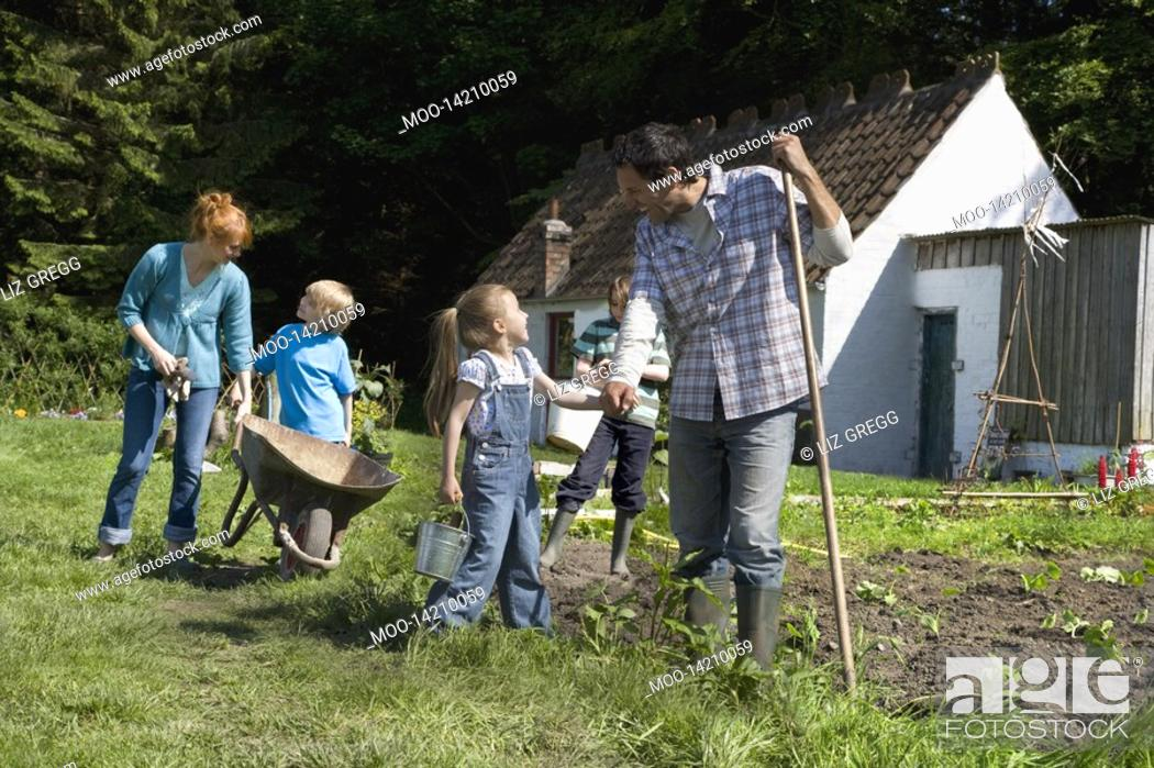 Stock Photo: Parents with three children 5-9 gardening outside cottage.