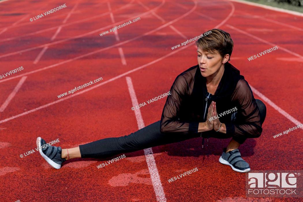 Stock Photo: Sportive woman stretching on tartan track.
