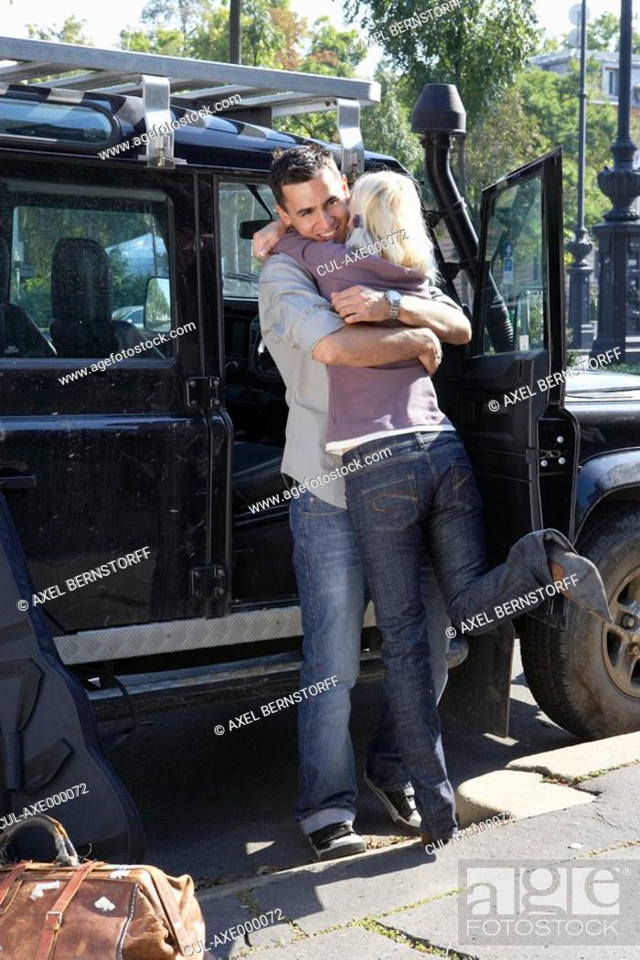 Stock Photo: Couple embracing by an SUV smiling.