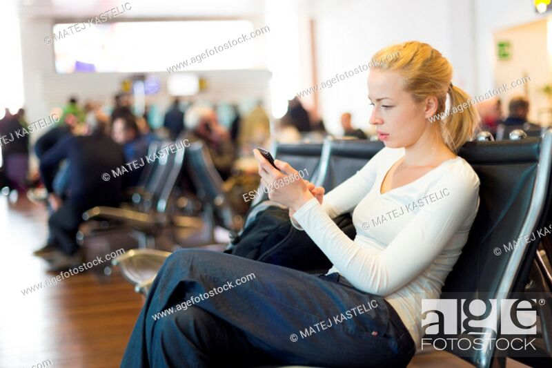 Stock Photo: Casual blond young woman using her cell phone while waiting to board a plane at the departure gates. Wireless network hotspot enabling people to access internet.