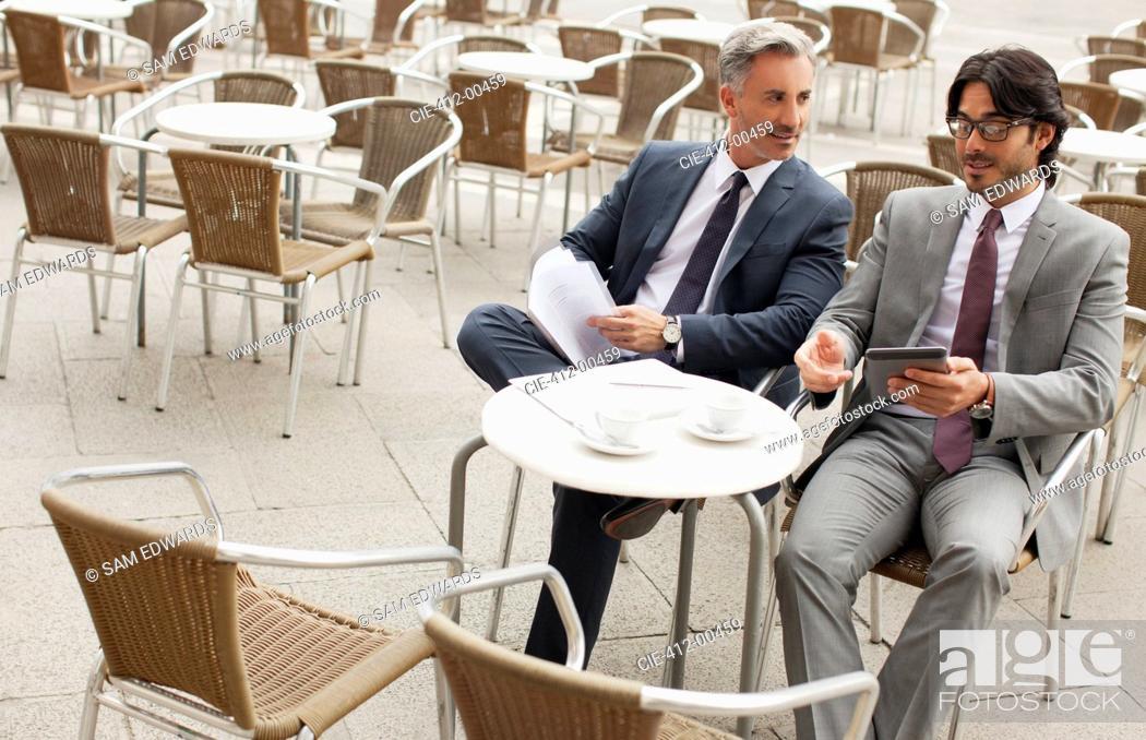 Stock Photo: Businessmen meeting at sidewalk cafe.