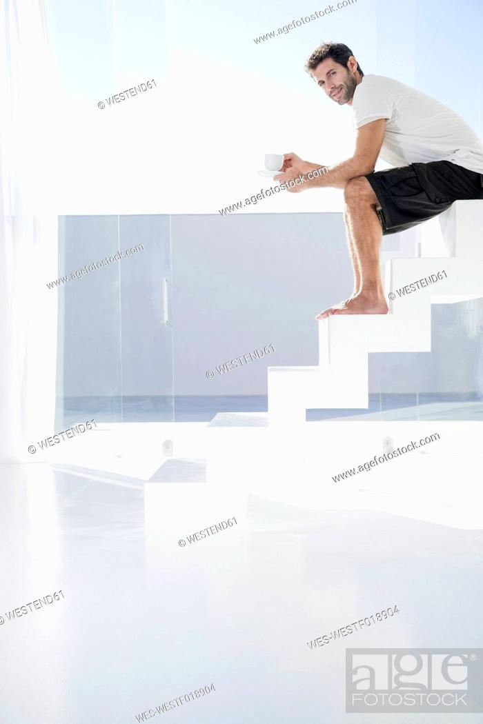 Stock Photo: Spain, Mid adult man sitting on stairway with cup.