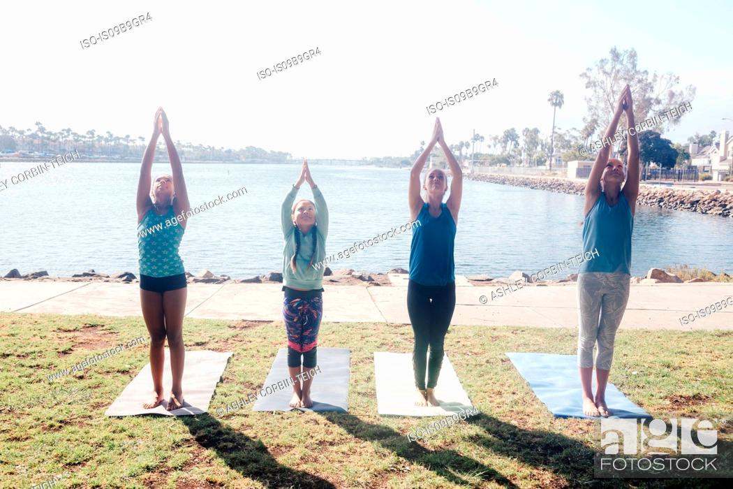 Stock Photo: Schoolgirls practicing yoga mountain pose by lakeside on school sports field.
