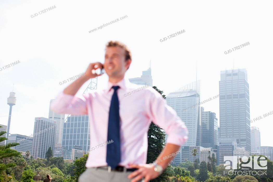 Stock Photo: Businessman talking on cell phone outdoors.
