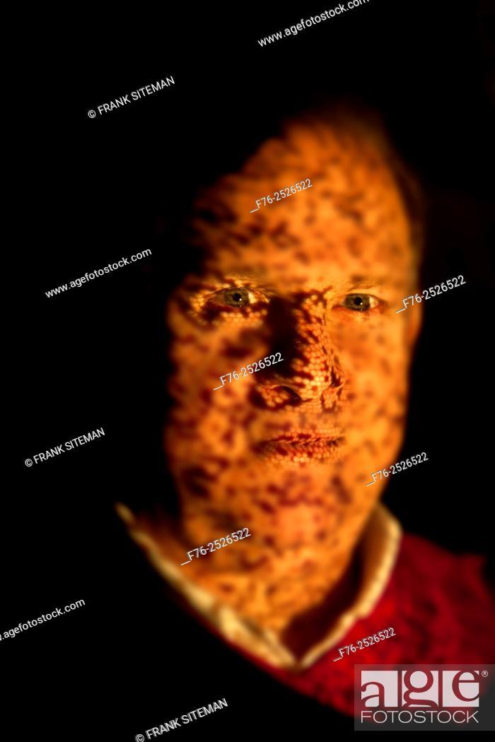 Stock Photo: Portrait of man illuminated by fiber optic light source, where dark spots indicate broken fibers in the bundle.