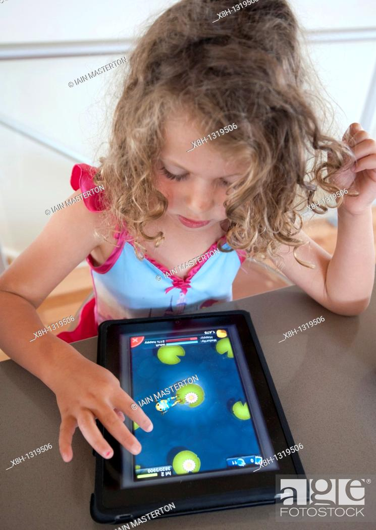 Stock Photo: Child playing computer game on an iPad tablet computer.
