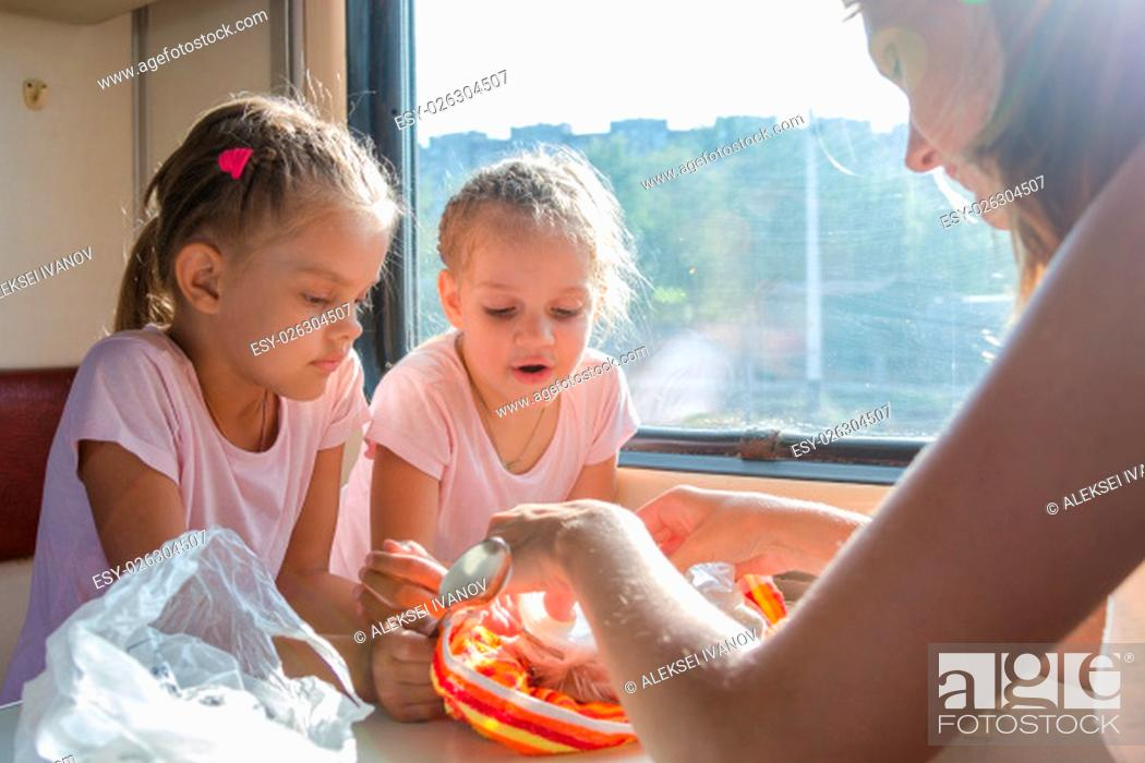 Stock Photo: My mother unpacks prepared home food for hungry children in second-class train carriage.