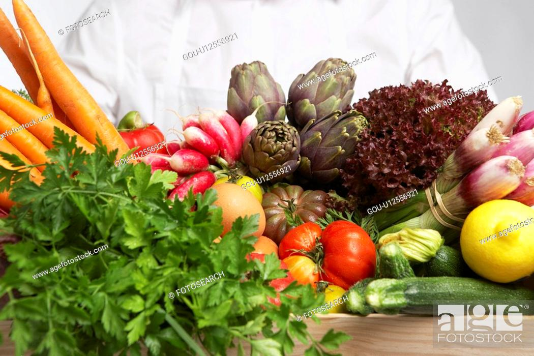 Stock Photo: Chef holding box of vegetables (close-up).