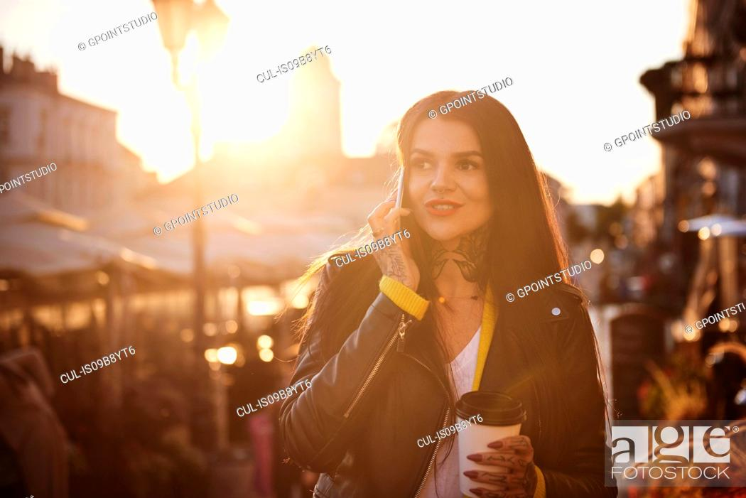 Stock Photo: Young woman walking outdoors, holding coffee cup, using smartphone, tattoos on hands and neck.