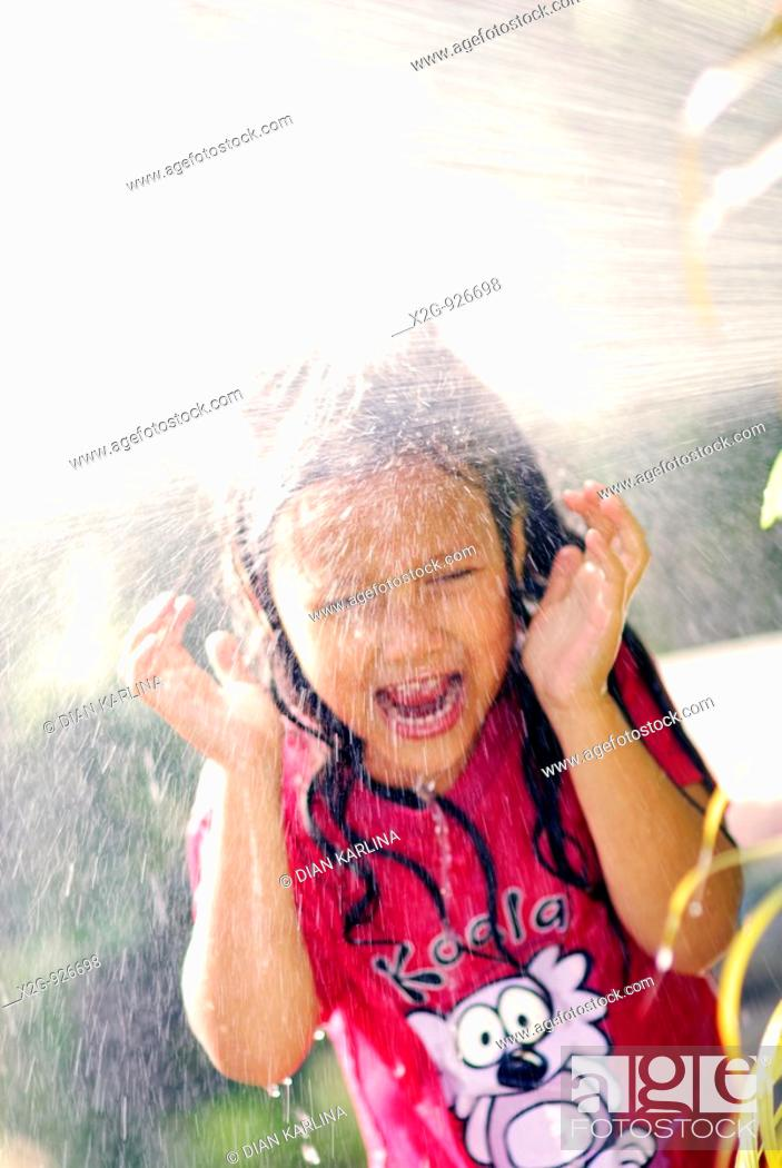 Stock Photo: A little girl splashed wit h water from a hose pipe.