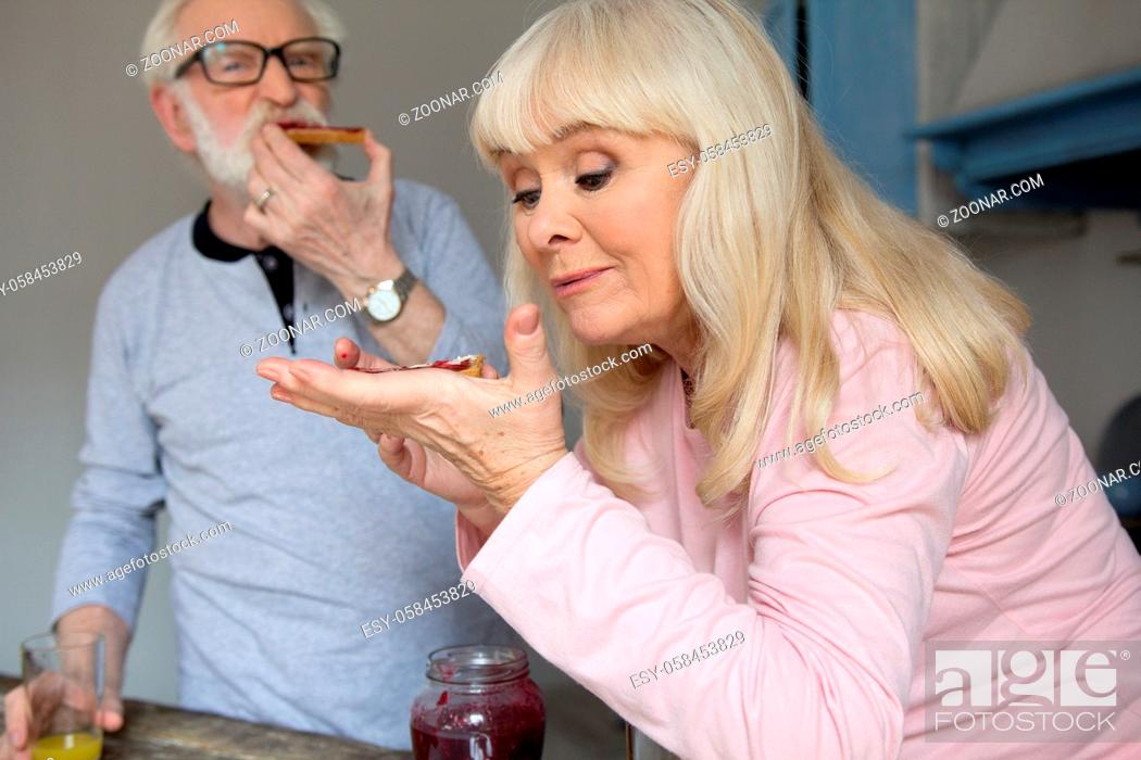 Stock Photo: Elderly married couple enjoying their snack. Charming old lady with blond hair eating bread with jelly with her husband in background.
