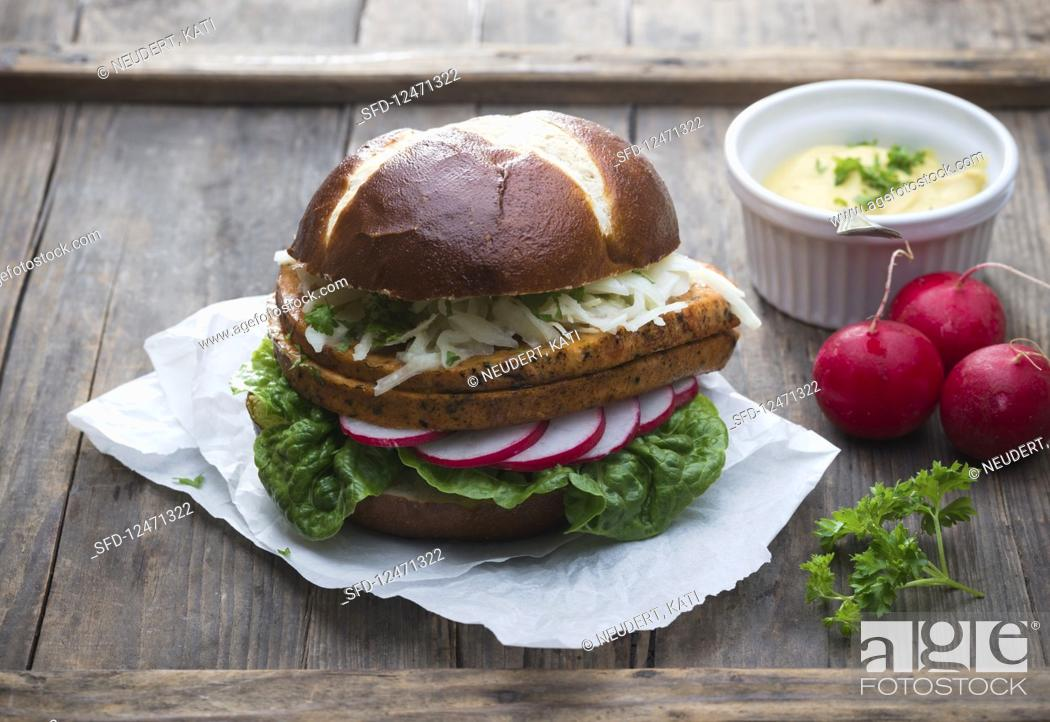 Stock Photo: A lye bread roll with vegan meatloaf, coleslaw, radishes, lettuce and mustard.