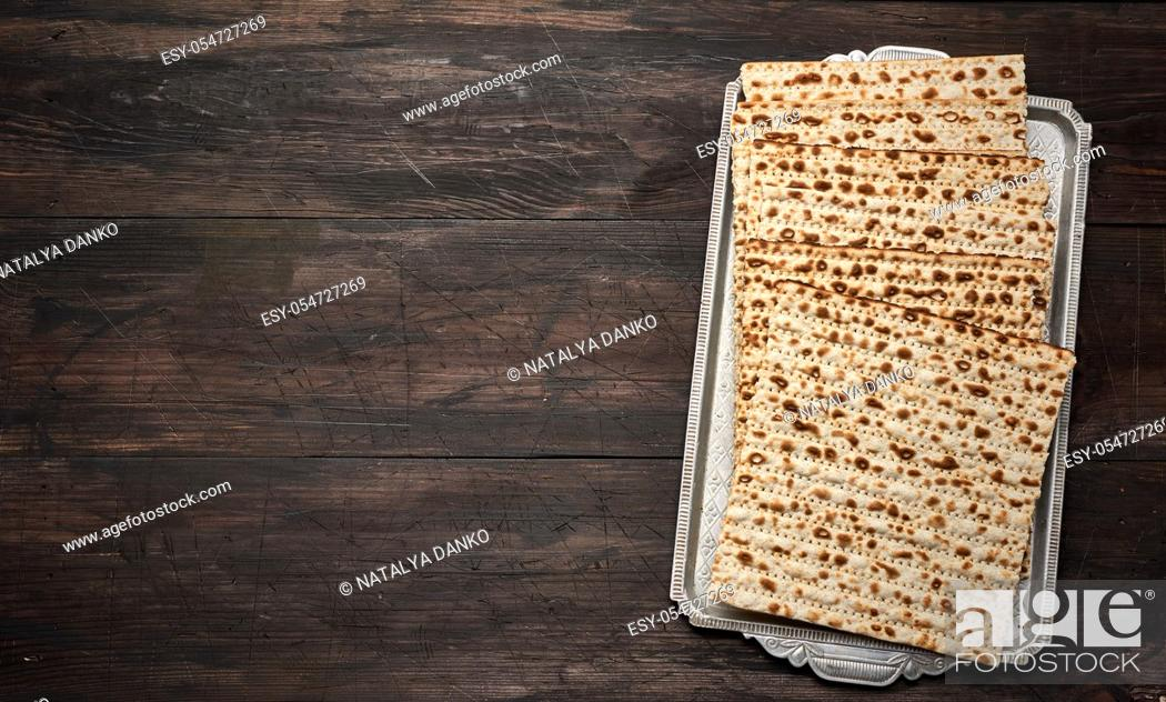 Stock Photo: stack of baked square matzoh on brown wooden background, top view, copy space.