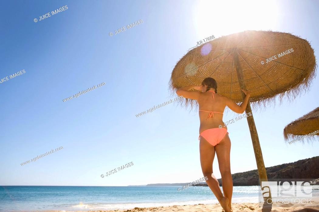 Stock Photo: Teenage girl standing under beach umbrella.