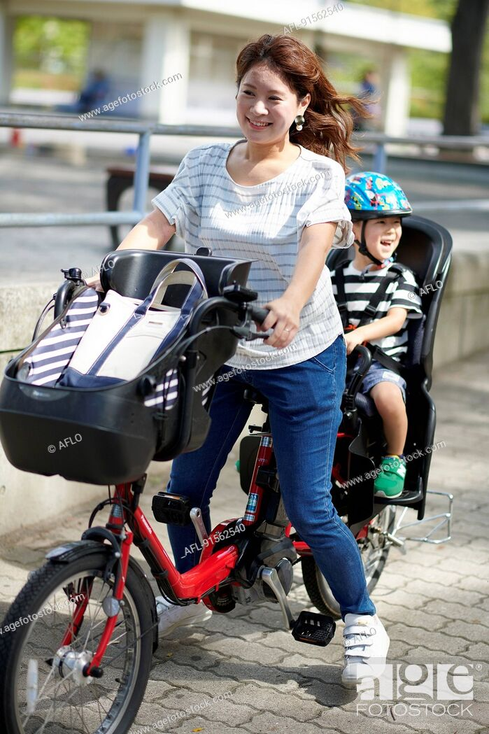 Stock Photo: Japanese mother and kid riding a bike.