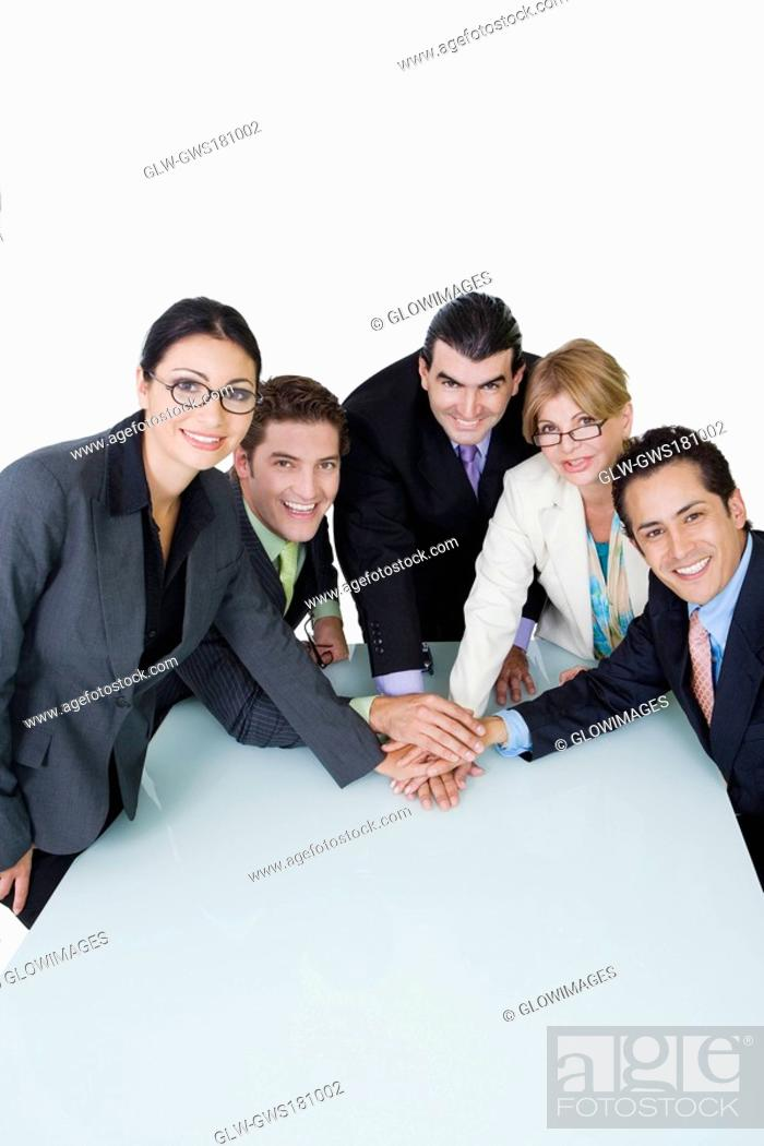 Stock Photo: Portrait of two businesswomen and three businessmen placing their hands on each other.