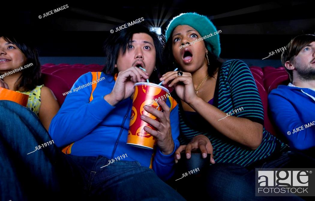 Stock Photo: Couple in cinema sharing drink, making faces, low angle view.
