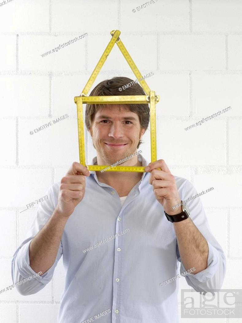 Stock Photo: Man with a folding rule looking like a house.