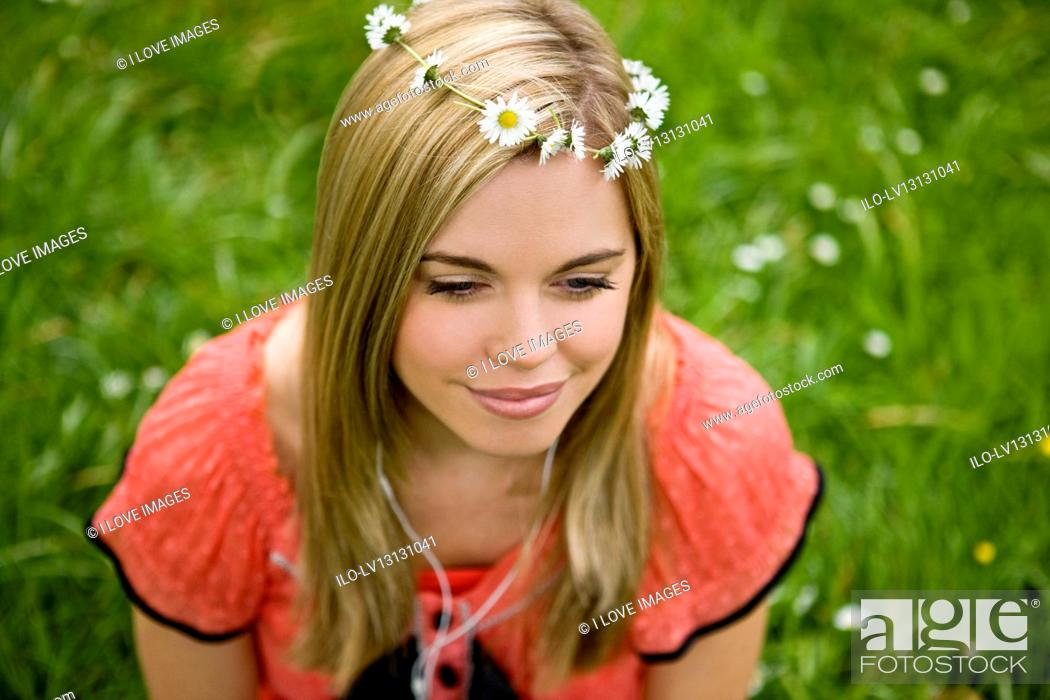 Stock Photo: A young woman sitting on the grass, listening to music.