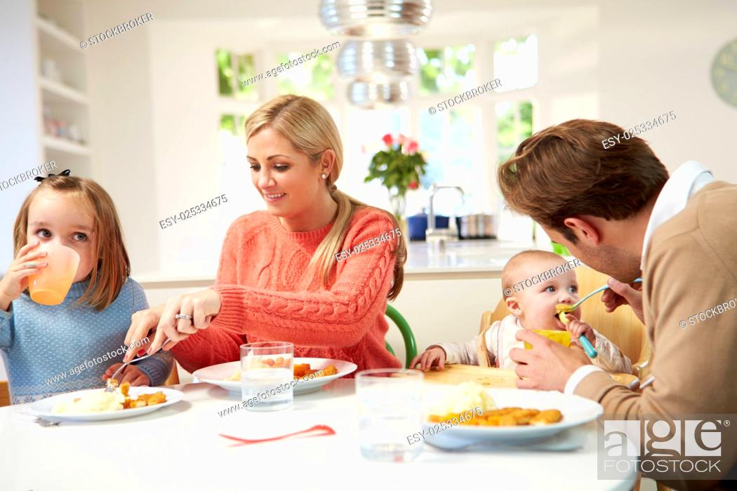 Stock Photo: Family With Young Baby Eating Meal At Home.