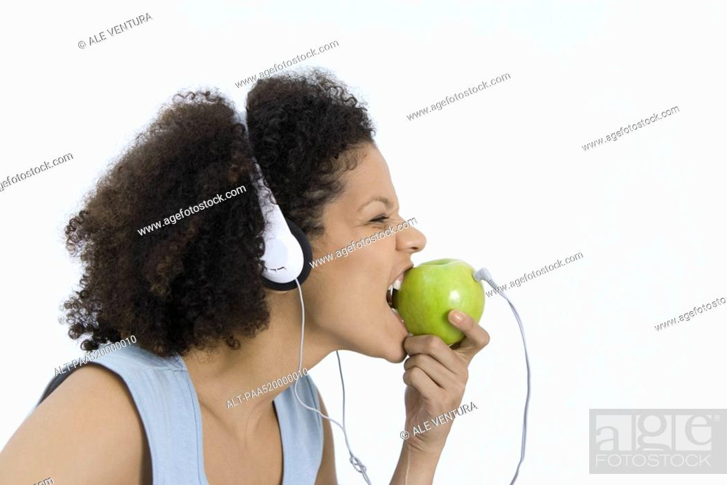 Stock Photo: Woman wearing headphones plugged into apple, biting into apple, profile.