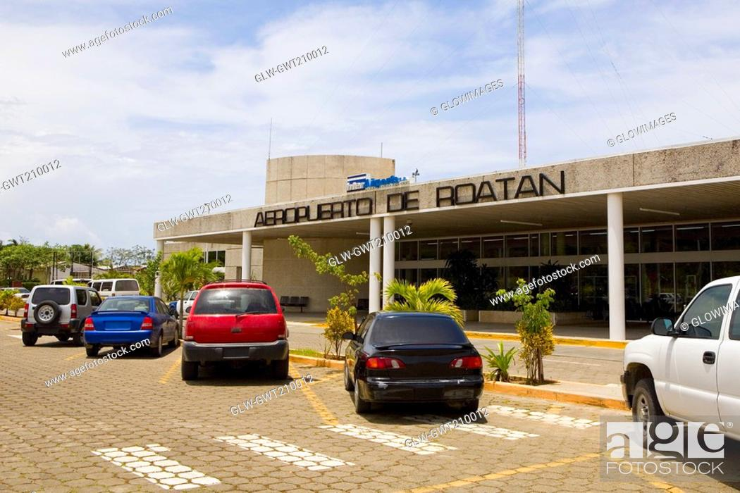 Stock Photo: Cars parked in front of an airport entrance, Roatan, Bay Islands, Honduras.