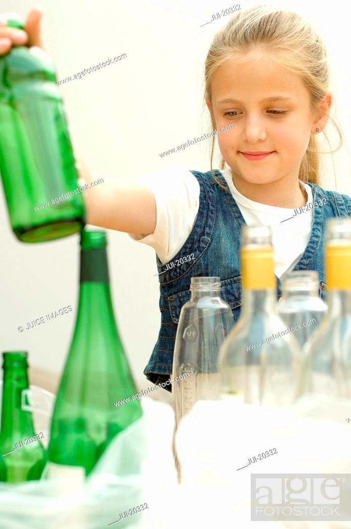 Stock Photo: Girl separating green plastic bottle clear glass bottle, Den Haag, Netherlands.