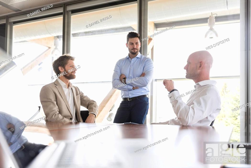 Stock Photo: Three businessmen discussing in conference room.
