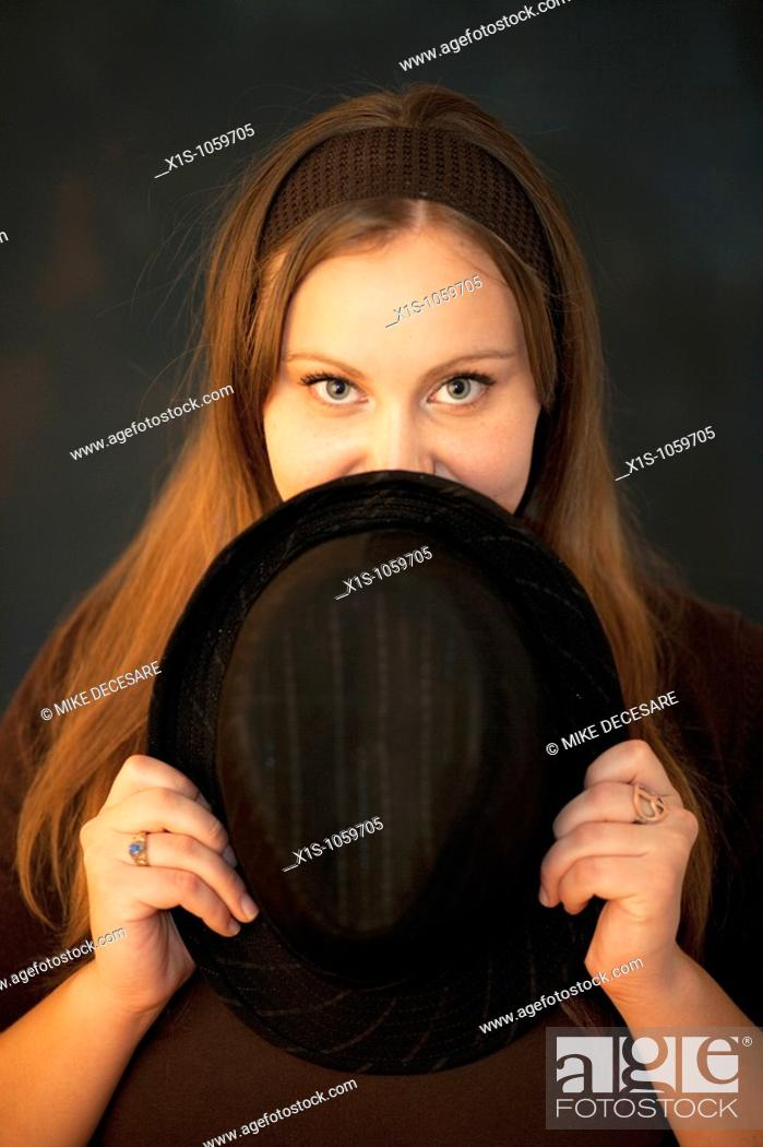Stock Photo: A young woman with dark, brown hair holds a man's hat up to her chin and hides part of her face with a playful expression in her eyes.