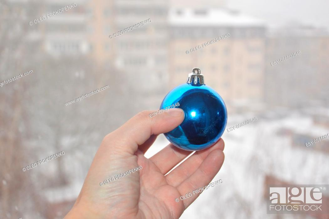 Stock Photo: A man holds Christmas tree toys in his hand on a background of the winter.